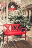 Banco rojo decorativo tradicional para relajarse en una feria de la ciudad Luz de la noche Navidad imagen de archivo libre de regalías