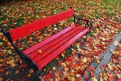 Banco rojo en el parque Fotos de archivo libres de regalías