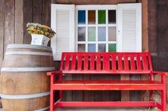 Banco rosso davanti ai multi vetri di colore della finestra. Fotografia Stock
