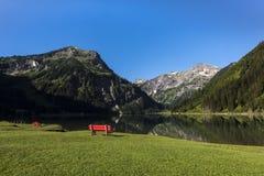 Banco rosso sul lago Vilsalpsee a Tannheim, montagne di Vilsalpseeberge, alta valle di Tannheimer Tal, Tirolo, Austria Fotografia Stock Libera da Diritti