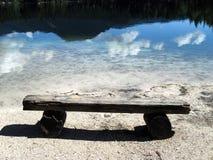 Banco simple viejo en la orilla del lago de la montaña imagenes de archivo