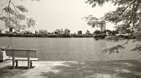 Banco solitario dalla riva del lago Fotografie Stock Libere da Diritti