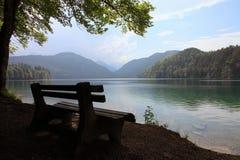 Banco solo al lado de un lago Imágenes de archivo libres de regalías