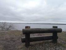 Banco sulla spiaggia in lago immagine stock