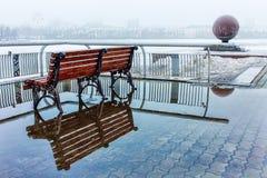 Banco in una pozza sulla neve della primavera della nebbia di Ekaterinburg dell'argine a marzo Fotografie Stock