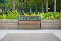 Banco vacío aislado en un parque público con el jardín foto de archivo