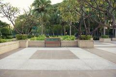 Banco vacío aislado en un parque público con el jardín imagen de archivo