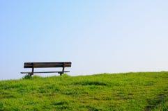 Banco vacío en una hierba verde Foto de archivo libre de regalías