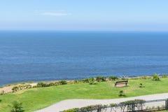 Banco vacío que hace frente hacia la costa del océano contra el cielo azul foto de archivo
