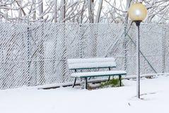 Banco vazio em um campo de jogos após a queda de neve imagem de stock royalty free
