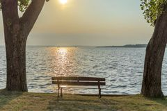 Banco vazio na costa do lago entre duas árvores foto de stock royalty free
