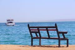 Banco vazio perto do mar e do navio enviado loneliness Partida do navio Banco perto da praia fotografia de stock