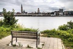 Banco vazio que negligencia a skyline de Antuérpia com o rio do schelde Imagens de Stock Royalty Free