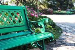 Banco verde del jardín en el fondo colorido de la imagen de la flor del parque imagen de archivo