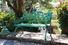 Banco verde del jardín en el fondo colorido de la imagen de la flor del parque fotografía de archivo libre de regalías