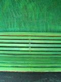 Banco verde en una pared verde Foto de archivo