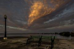 Banco verde rustico e vecchia posta leggera con la nuvola arancio incredibile nel fondo Fotografie Stock