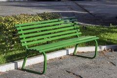Banco verde vacío en un parque público fotos de archivo