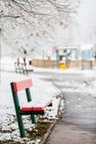 Banco vermelho em um parque nevado, campo de jogos das crianças no fundo Fotografia de Stock Royalty Free