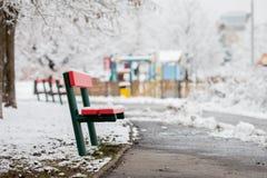 Banco vermelho em um parque nevado, campo de jogos das crianças no fundo Foto de Stock
