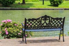 Banco vicino al lago nel giardino tropicale Immagine Stock