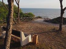 Banco vuoto su un bello wiew del mare alla luce dorata di sera fotografia stock libera da diritti