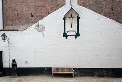 Banco y crucifijo en el Beguinage Bélgica Imagenes de archivo