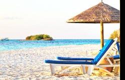 Banco y paraguas de la playa de Maldivas fotografía de archivo