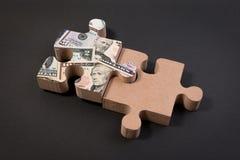 Banconota americana del dollaro sopra il puzzle con lo spazio della copia Fotografie Stock Libere da Diritti