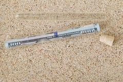 Banconota del dollaro di 100 americani dentro un tubo con il coperchio del sughero rimosso Fotografie Stock Libere da Diritti