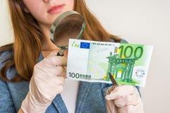 Banconota della falsificazione di osservazione della donna con la lente d'ingrandimento fotografia stock