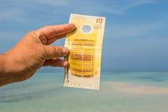 Banconota delle Maldive in mano femminile del ` s Fotografie Stock