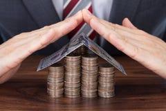 Banconota di Sheltering Coins And dell'uomo d'affari nella forma della Camera Immagini Stock Libere da Diritti