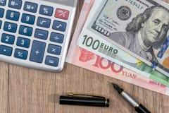 Banconota di yuan del dollaro americano, dell'euro e di cinese con il calcolatore Immagini Stock