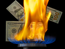 Banconota in dollari su fuoco in fiamma del bruciatore a gas Fotografia Stock Libera da Diritti