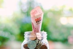 Banconota, soldi tailandesi di valuta di 100 baht che crescono dal ja di vetro Immagini Stock