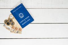 Banconote brasiliane dei soldi, monete brasiliane e permesso di lavoro su bianco immagini stock libere da diritti