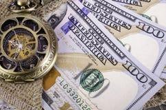 Banconote cento dollari, tela da imballaggio e orologi da tasca Immagine Stock