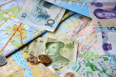 Banconote cinesi e monete sull'mappe cinesi Fotografia Stock Libera da Diritti