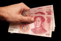 Banconote cinesi in mano maschio isolata sul nero Fotografia Stock
