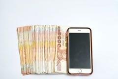 Banconote dei soldi e dello Smart Phone su fondo bianco isolato dentro fotografie stock
