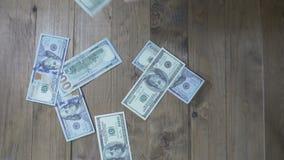 Banconote del dollaro che cadono su una Tabella di legno Movimento lento video d archivio
