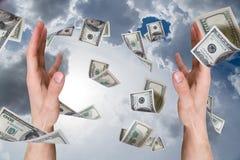 Banconote del dollaro che cadono sulle giovani mani maschii Fotografia Stock