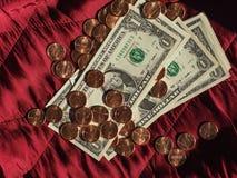 Banconote del dollaro e moneta, Stati Uniti sopra il fondo rosso del velluto fotografia stock libera da diritti