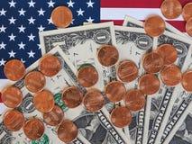 Banconote del dollaro e monete e bandiera degli Stati Uniti Fotografia Stock