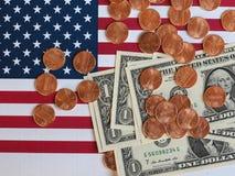 Banconote del dollaro e monete e bandiera degli Stati Uniti Immagine Stock