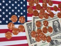 Banconote del dollaro e monete e bandiera degli Stati Uniti Fotografie Stock