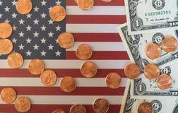 Banconote del dollaro e monete e bandiera degli Stati Uniti Fotografie Stock Libere da Diritti