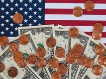 Banconote del dollaro e monete e bandiera degli Stati Uniti Immagini Stock