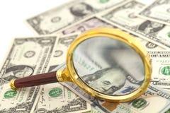 Banconote del dollaro sotto la lente d'ingrandimento Immagine Stock